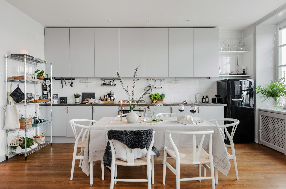 Eat-in kitchen - mid-sized scandinavian single-wall medium tone wood floor eat-in kitchen idea in Stockholm with flat-panel cabinets, gray cabinets, stainless steel countertops, white backsplash, black appliances and no island