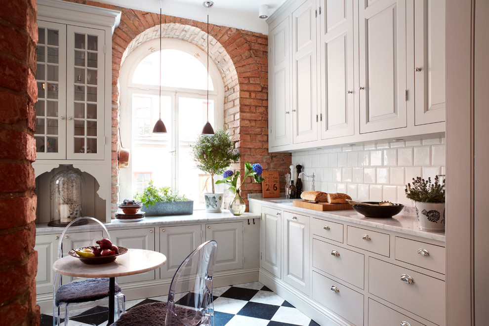 Eat-in kitchen - mid-sized country l-shaped ceramic tile eat-in kitchen idea in Stockholm with an undermount sink, raised-panel cabinets, beige cabinets, marble countertops, white backsplash, subway tile backsplash and no island