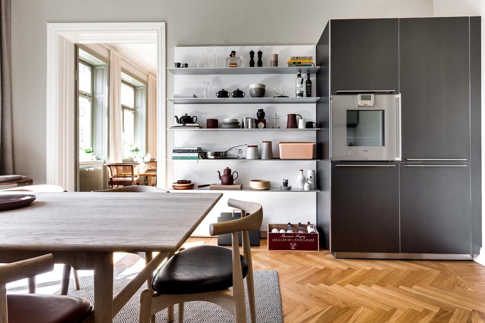 Bild på ett mellanstort skandinaviskt kök, med öppna hyllor, svarta vitvaror och mellanmörkt trägolv