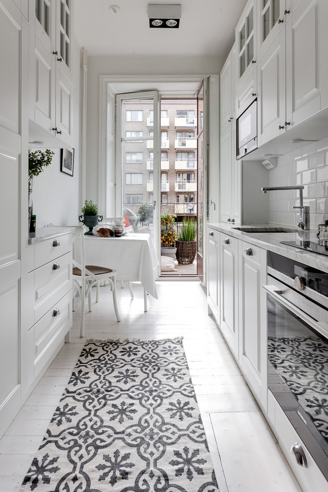 Eat-in kitchen - mid-sized scandinavian galley painted wood floor eat-in kitchen idea in Stockholm with an undermount sink, raised-panel cabinets, white cabinets, white backsplash, subway tile backsplash, stainless steel appliances and marble countertops