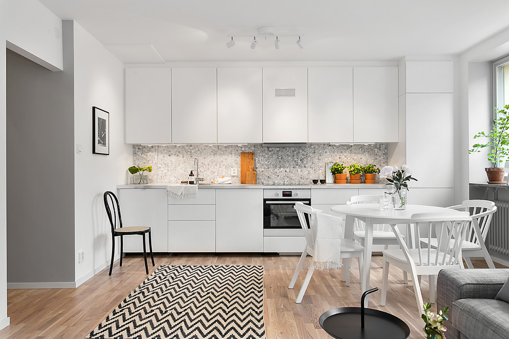 Mid-sized danish single-wall medium tone wood floor open concept kitchen photo in Stockholm with flat-panel cabinets, white cabinets, gray backsplash, white appliances and no island