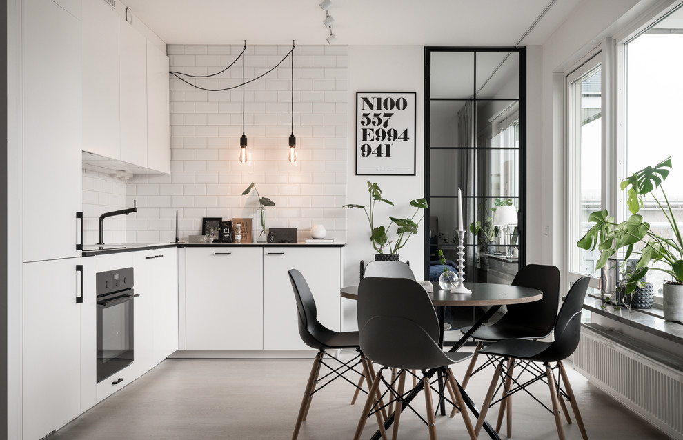 Mid-sized danish l-shaped concrete floor and white floor kitchen photo in Stockholm with flat-panel cabinets, white cabinets, paneled appliances and no island