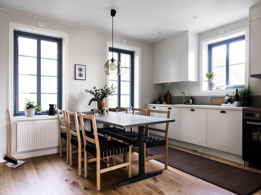 Foto på ett skandinaviskt linjärt kök och matrum, med släta luckor, vita skåp, svarta vitvaror, mellanmörkt trägolv och brunt golv