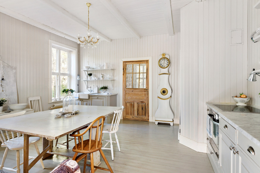 Eat-in kitchen - mid-sized shabby-chic style l-shaped painted wood floor eat-in kitchen idea in Stockholm with a farmhouse sink, raised-panel cabinets, gray cabinets, stainless steel appliances, no island and marble countertops