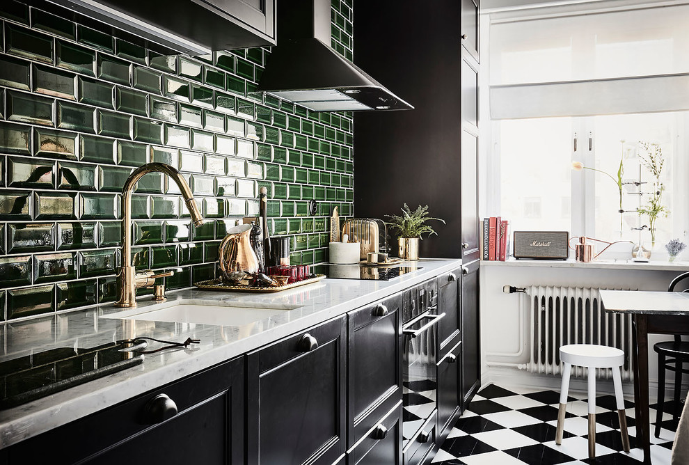 Design ideas for a medium sized scandinavian single-wall kitchen/diner in Gothenburg with a submerged sink, recessed-panel cabinets, black cabinets, green splashback, metro tiled splashback, black appliances, no island, marble worktops, painted wood flooring and multi-coloured floors.