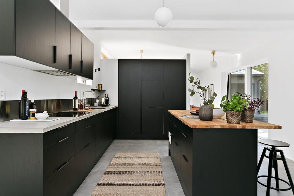 Foto de cocinas en L nórdica con armarios con paneles lisos, puertas de armario negras, encimera de madera, electrodomésticos con paneles, una isla y suelo gris