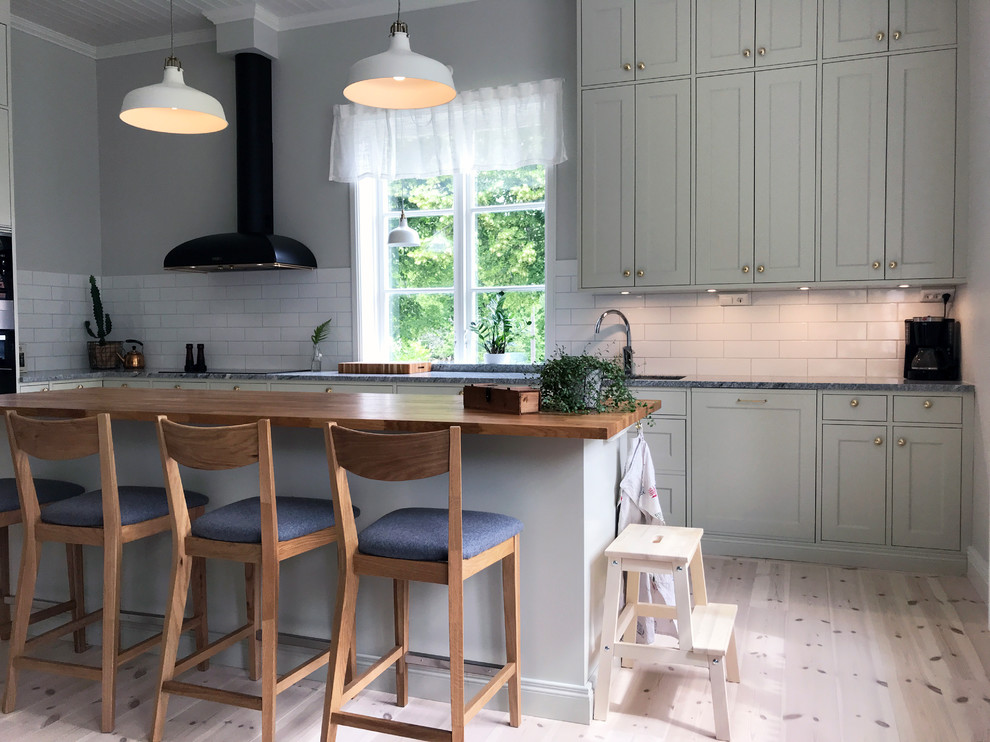 Kitchen - huge cottage l-shaped kitchen idea in Other with a single-bowl sink, shaker cabinets, green cabinets, granite countertops, white backsplash, porcelain backsplash, stainless steel appliances, an island and gray countertops