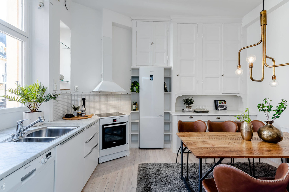 Eat-in kitchen - scandinavian l-shaped light wood floor and beige floor eat-in kitchen idea in Stockholm with a double-bowl sink, recessed-panel cabinets, white cabinets, white backsplash, white appliances, no island and gray countertops