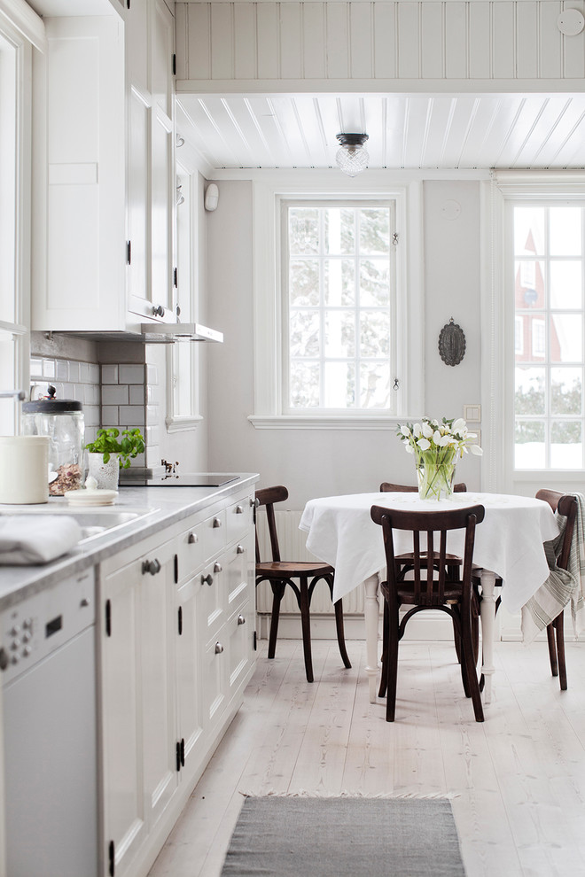 Eat-in kitchen - mid-sized country single-wall light wood floor eat-in kitchen idea in Stockholm with a double-bowl sink, recessed-panel cabinets, white cabinets, white backsplash, subway tile backsplash, marble countertops and no island