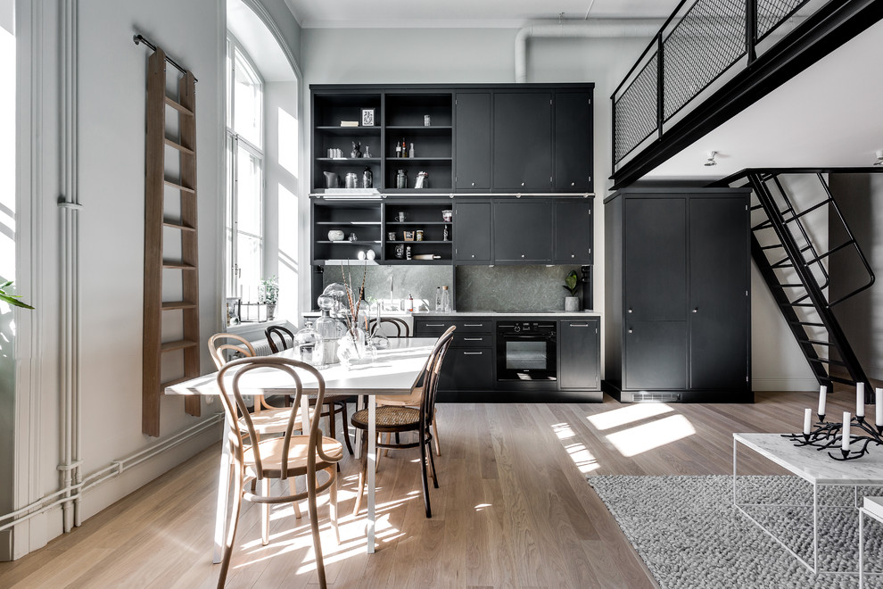 Example of a mid-sized danish single-wall light wood floor open concept kitchen design in Stockholm with limestone countertops, a farmhouse sink, flat-panel cabinets, black cabinets, gray backsplash, stone slab backsplash, black appliances and no island