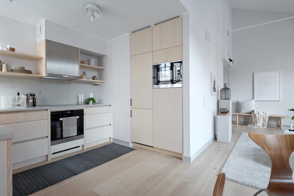 Idéer för ett mellanstort minimalistiskt kök, med en undermonterad diskho, bänkskiva i kalksten, stänkskydd i kalk, rostfria vitvaror och ljust trägolv