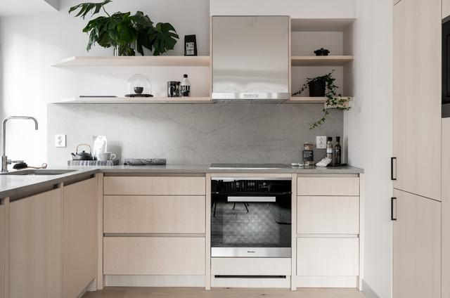 Esempio di una piccola cucina nordica con ante lisce, ante in legno chiaro, top in cemento, parquet chiaro, penisola, pavimento beige, lavello sottopiano, paraspruzzi grigio e elettrodomestici neri