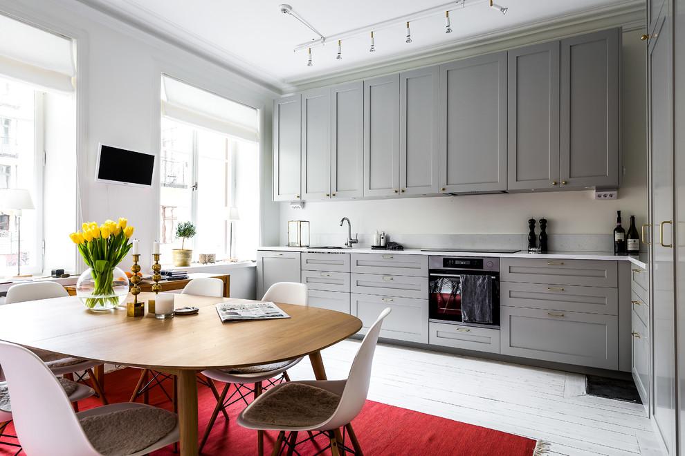 Modelo de cocina comedor en L, nórdica, sin isla, con armarios estilo shaker, puertas de armario grises, salpicadero verde, electrodomésticos negros, suelo de madera pintada y suelo blanco
