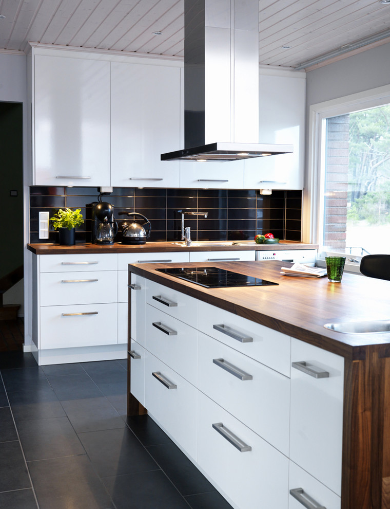 Mid-sized minimalist limestone floor kitchen photo in Orebro with flat-panel cabinets, white cabinets, wood countertops and an island