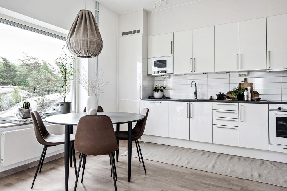 Example of a mid-sized danish single-wall light wood floor and beige floor eat-in kitchen design in Gothenburg with flat-panel cabinets, white cabinets, white backsplash, no island and black countertops