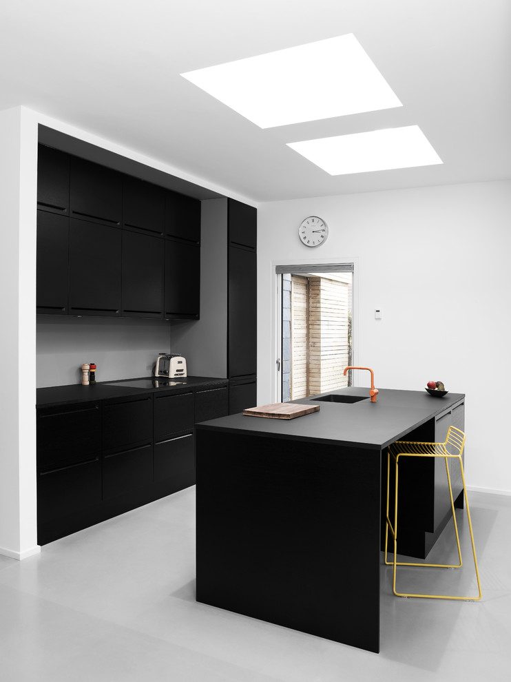 Inspiration for a mid-sized scandinavian galley linoleum floor enclosed kitchen remodel in Copenhagen with an integrated sink, flat-panel cabinets, black cabinets, wood countertops, black appliances and an island