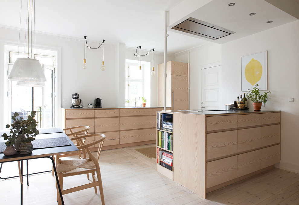 Mid-sized danish galley light wood floor and beige floor eat-in kitchen photo in Copenhagen with flat-panel cabinets, light wood cabinets and a peninsula