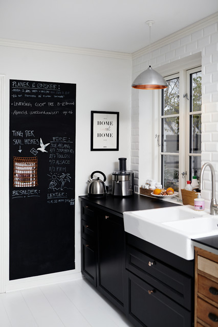 Cottage painted wood floor kitchen photo in Wiltshire with a farmhouse sink, recessed-panel cabinets, black cabinets, white backsplash and subway tile backsplash