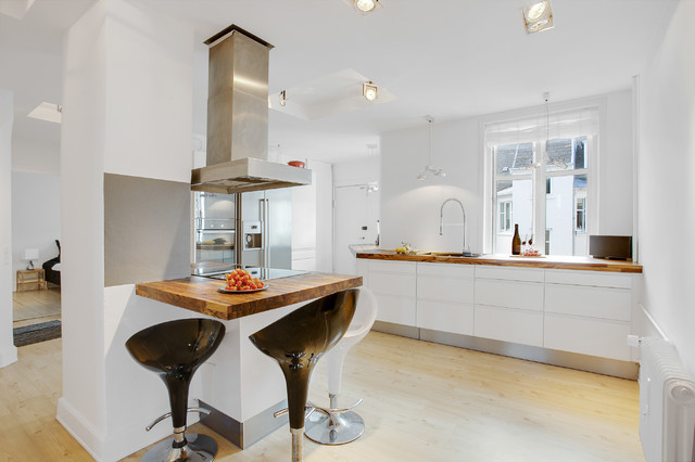 Medium sized scandi l-shaped enclosed kitchen in Miami with a submerged sink, flat-panel cabinets, white cabinets, wood worktops, grey splashback, stainless steel appliances, light hardwood flooring, an island and glass sheet splashback.