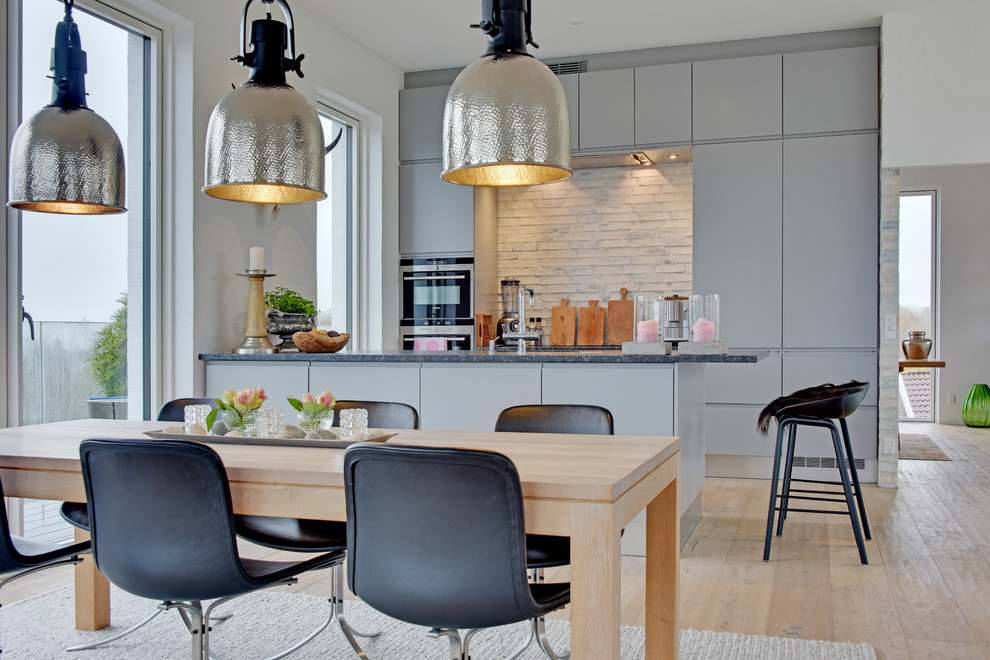 Inspiration for a scandinavian light wood floor kitchen remodel in Aarhus with flat-panel cabinets, gray cabinets, marble countertops, brick backsplash and a peninsula