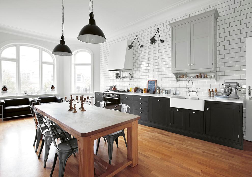 Einzeilige, Große Industrial Wohnküche ohne Insel mit Unterbauwaschbecken, Schrankfronten mit vertiefter Füllung, schwarzen Schränken, Arbeitsplatte aus Recyclingglas, schwarzen Elektrogeräten und braunem Holzboden in Kopenhagen