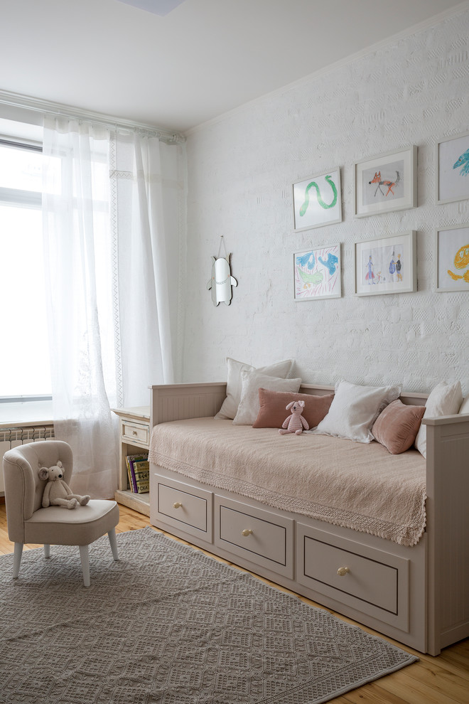 Example of a transitional girl medium tone wood floor and brown floor nursery design in Moscow with white walls