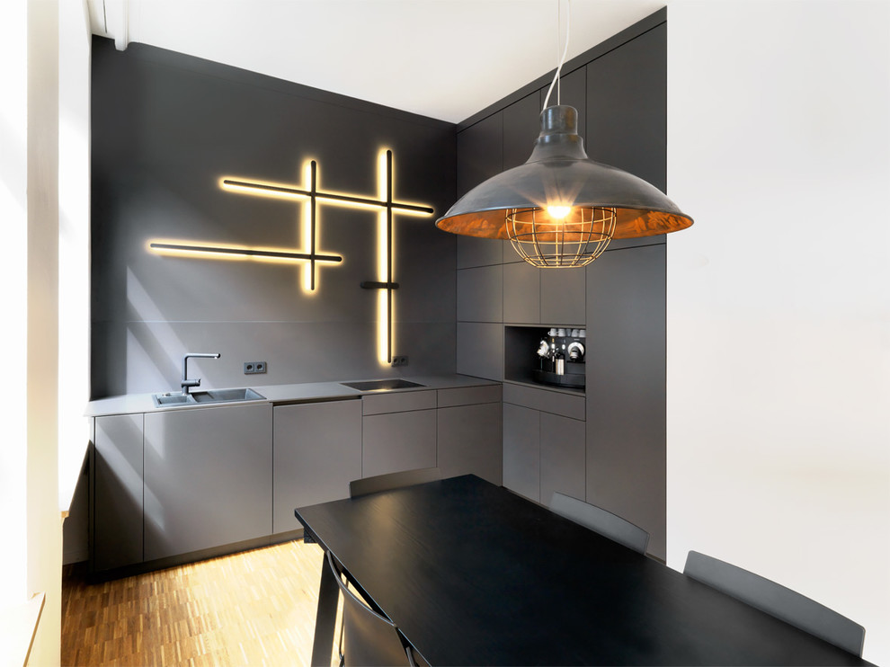Example of a small urban medium tone wood floor kitchen design in Nuremberg with a drop-in sink, flat-panel cabinets, black cabinets and black backsplash