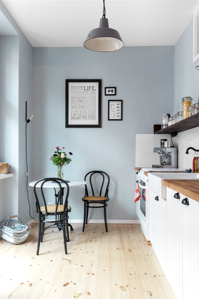 Example of a small danish single-wall light wood floor eat-in kitchen design in Berlin with a farmhouse sink, white cabinets, wood countertops, white backsplash, recessed-panel cabinets, white appliances, ceramic backsplash and no island