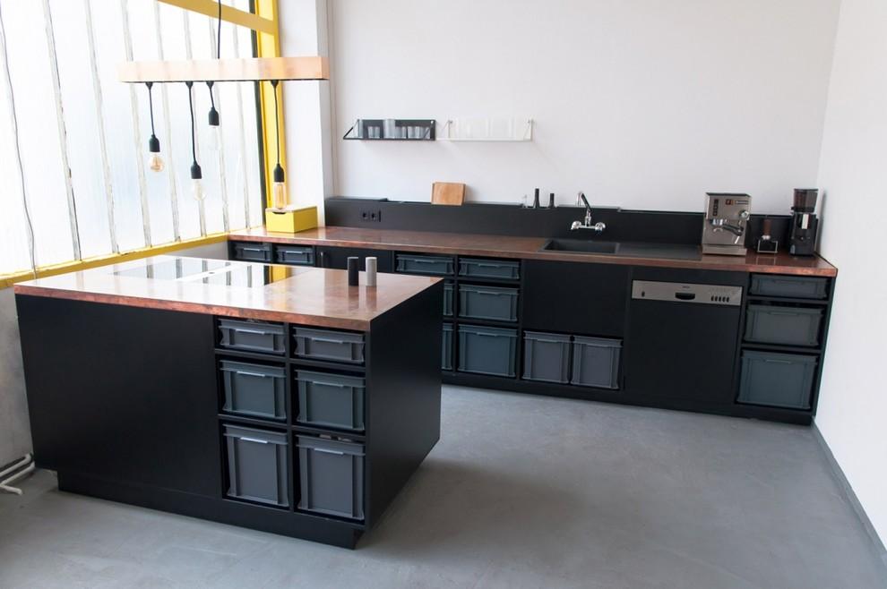 Imagen de cocina lineal, industrial, de tamaño medio, abierta, con fregadero encastrado, puertas de armario negras, encimera de cobre, salpicadero blanco, electrodomésticos negros, suelo de cemento y una isla