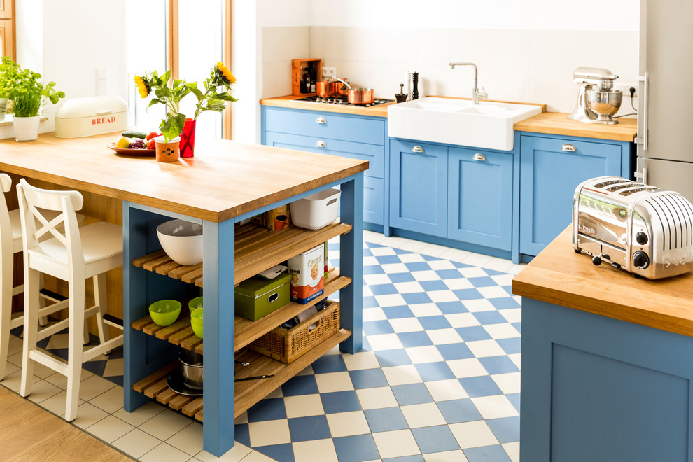 Small danish galley ceramic tile open concept kitchen photo in Cologne with a double-bowl sink, shaker cabinets, blue cabinets, wood countertops, white backsplash, ceramic backsplash, stainless steel appliances and an island