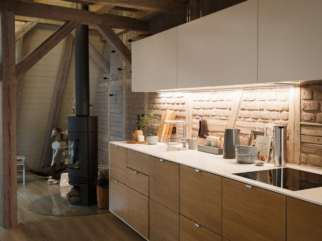 Inspiration for a small scandinavian single-wall medium tone wood floor and brown floor open concept kitchen remodel in Berlin with an integrated sink, flat-panel cabinets, medium tone wood cabinets, brown backsplash, brick backsplash, black appliances and no island