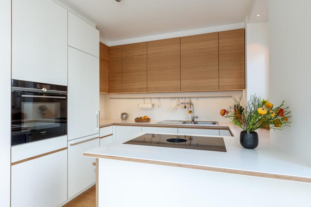 Offene, Mittelgroße Moderne Küche in U-Form mit Einbauwaschbecken, flächenbündigen Schrankfronten, weißen Schränken, Mineralwerkstoff-Arbeitsplatte, Küchenrückwand in Weiß, schwarzen Elektrogeräten, braunem Holzboden, Kücheninsel, braunem Boden, weißer Arbeitsplatte und eingelassener Decke in München