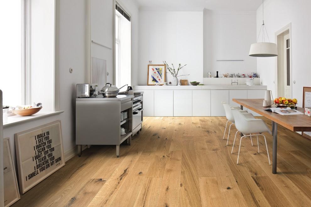 Moderne Küche ohne Insel in L-Form mit flächenbündigen Schrankfronten, weißen Schränken, braunem Holzboden, braunem Boden und weißer Arbeitsplatte