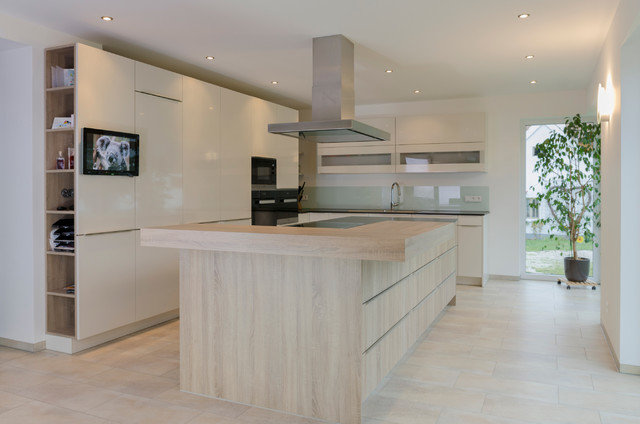 Eat-in kitchen - huge contemporary l-shaped limestone floor eat-in kitchen idea in Nuremberg with flat-panel cabinets, white cabinets, wood countertops, white backsplash, glass sheet backsplash, stainless steel appliances and an island
