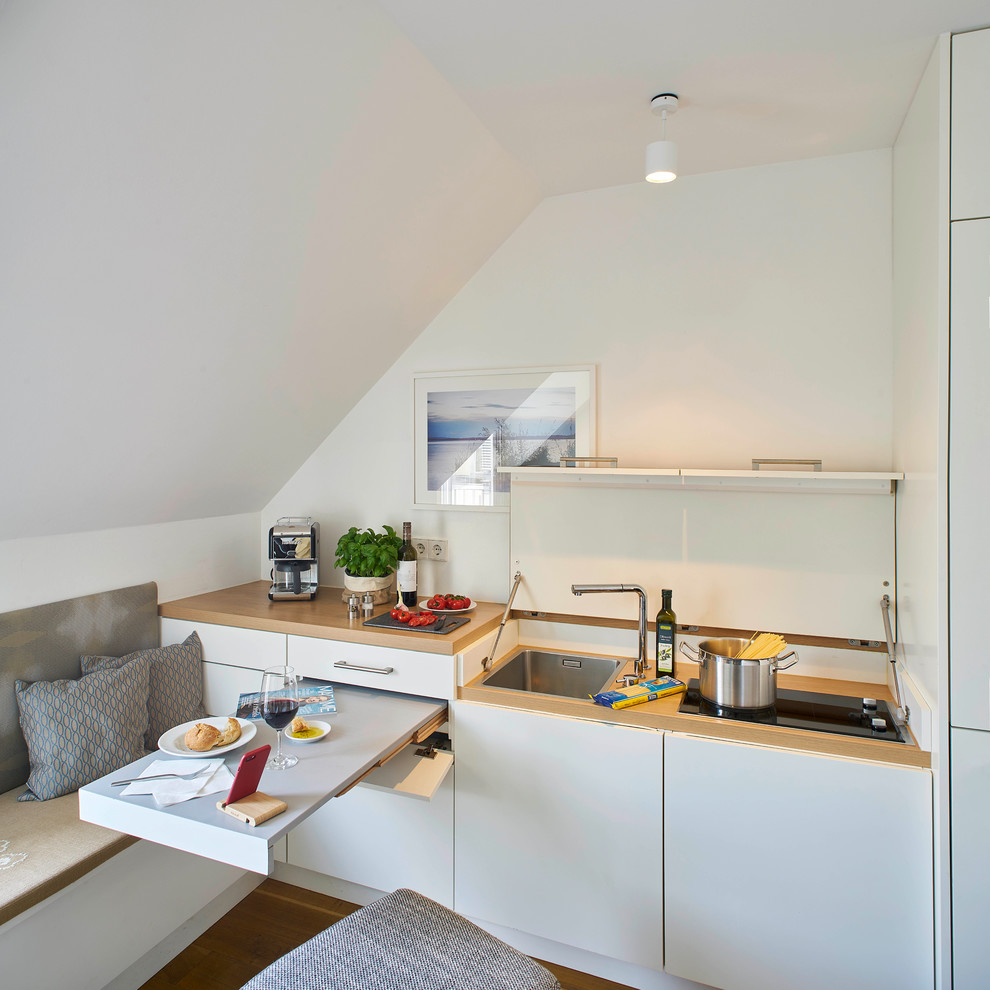 Eat-in kitchen - small contemporary single-wall medium tone wood floor and brown floor eat-in kitchen idea in Stuttgart with flat-panel cabinets, white cabinets, laminate countertops, white backsplash, paneled appliances, beige countertops and an undermount sink