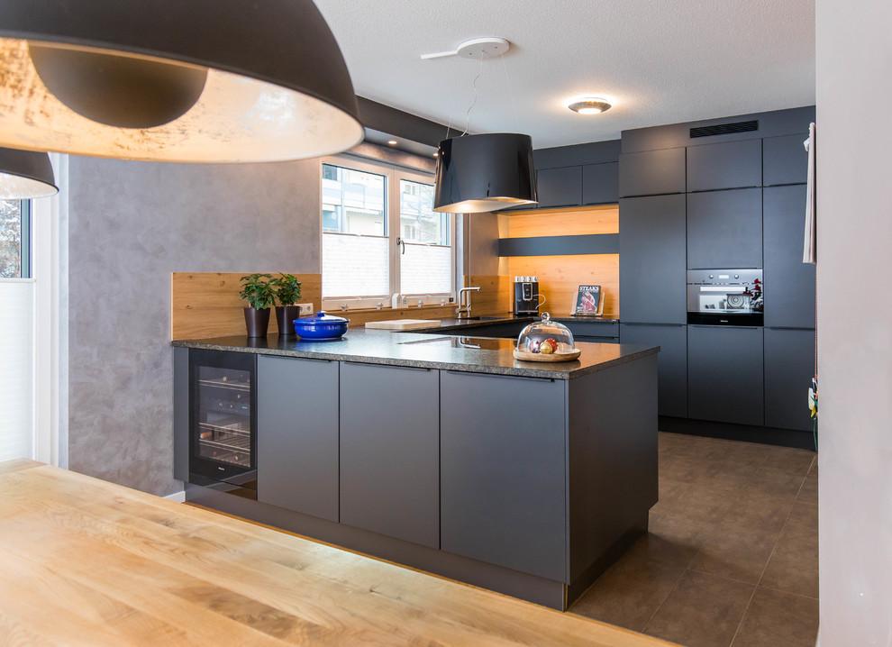 Mittelgroße Moderne Wohnküche in U-Form mit schwarzen Schränken, Granit-Arbeitsplatte, Halbinsel, integriertem Waschbecken, flächenbündigen Schrankfronten, Küchenrückwand in Braun, Rückwand aus Holz, schwarzen Elektrogeräten und braunem Boden in Nürnberg