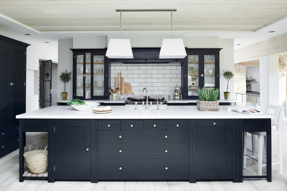 Large elegant galley painted wood floor open concept kitchen photo in Dusseldorf with glass-front cabinets, black cabinets, white backsplash, subway tile backsplash and an island