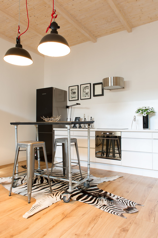 Inspiration for a mid-sized industrial single-wall medium tone wood floor eat-in kitchen remodel in Dusseldorf with flat-panel cabinets, white cabinets, white backsplash, no island and black appliances