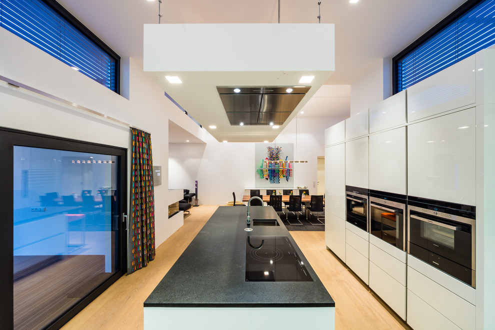 Open concept kitchen - large contemporary single-wall light wood floor open concept kitchen idea in Frankfurt with an undermount sink, flat-panel cabinets, white cabinets, black appliances, granite countertops and an island