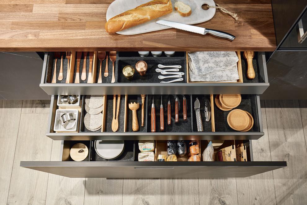 Offene Moderne Küche mit Arbeitsplatte aus Holz, schwarzen Schränken und brauner Arbeitsplatte in Nürnberg