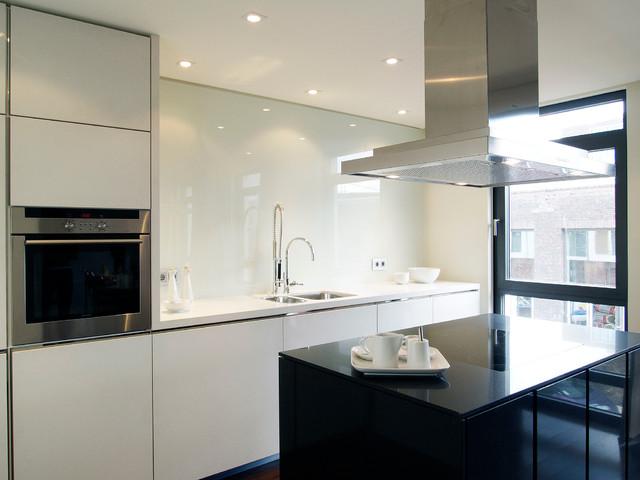 Offene schwarz-weiße Küche mit Kücheninsel / Open-plan black ...