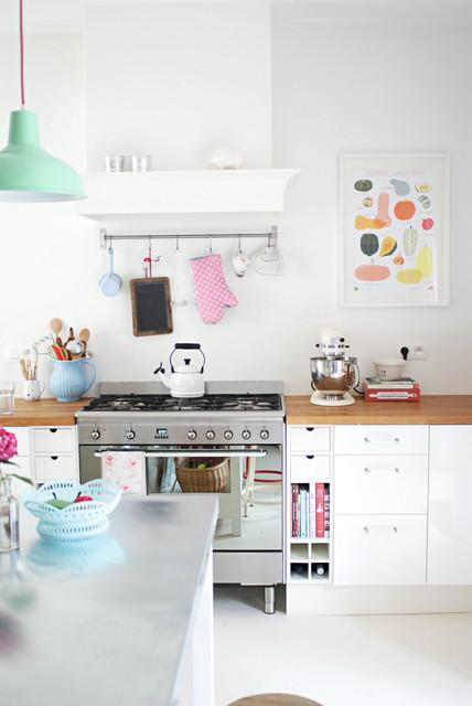 Inspiration pour une cuisine bohème avec un placard à porte plane, des portes de placard blanches, un plan de travail en bois, un électroménager en acier inoxydable et un îlot central.
