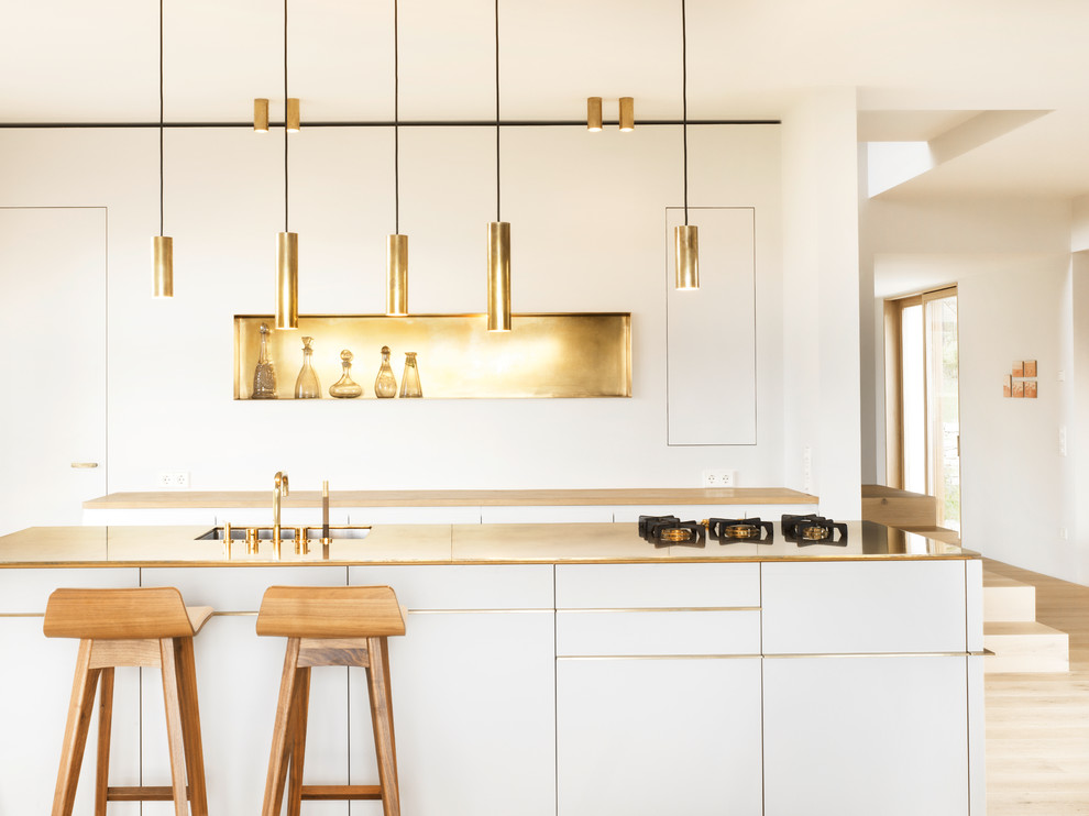 Kitchen - scandinavian light wood floor kitchen idea in Munich with an undermount sink, flat-panel cabinets, white cabinets, white backsplash, paneled appliances and an island