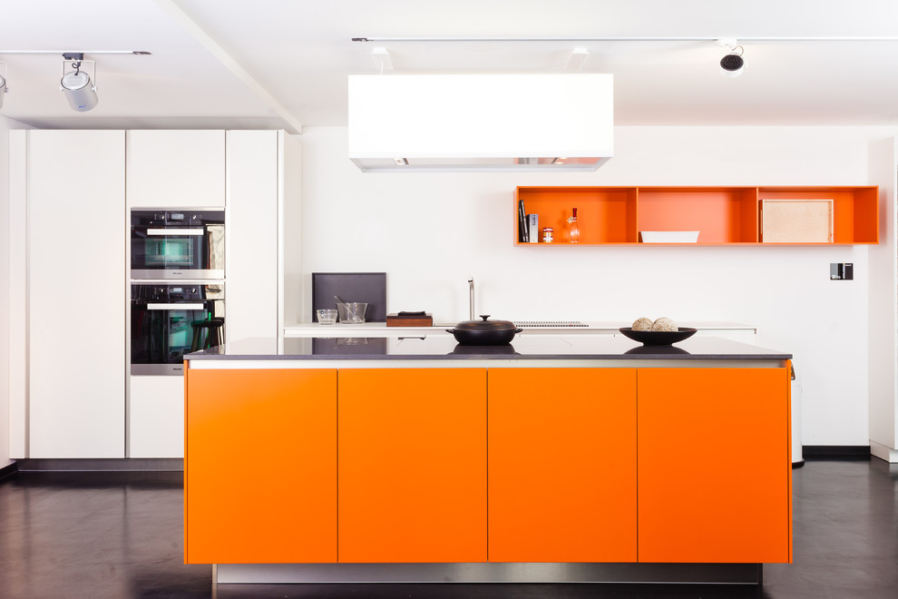 Large trendy concrete floor kitchen photo in Frankfurt with flat-panel cabinets, orange cabinets, an island and stainless steel appliances
