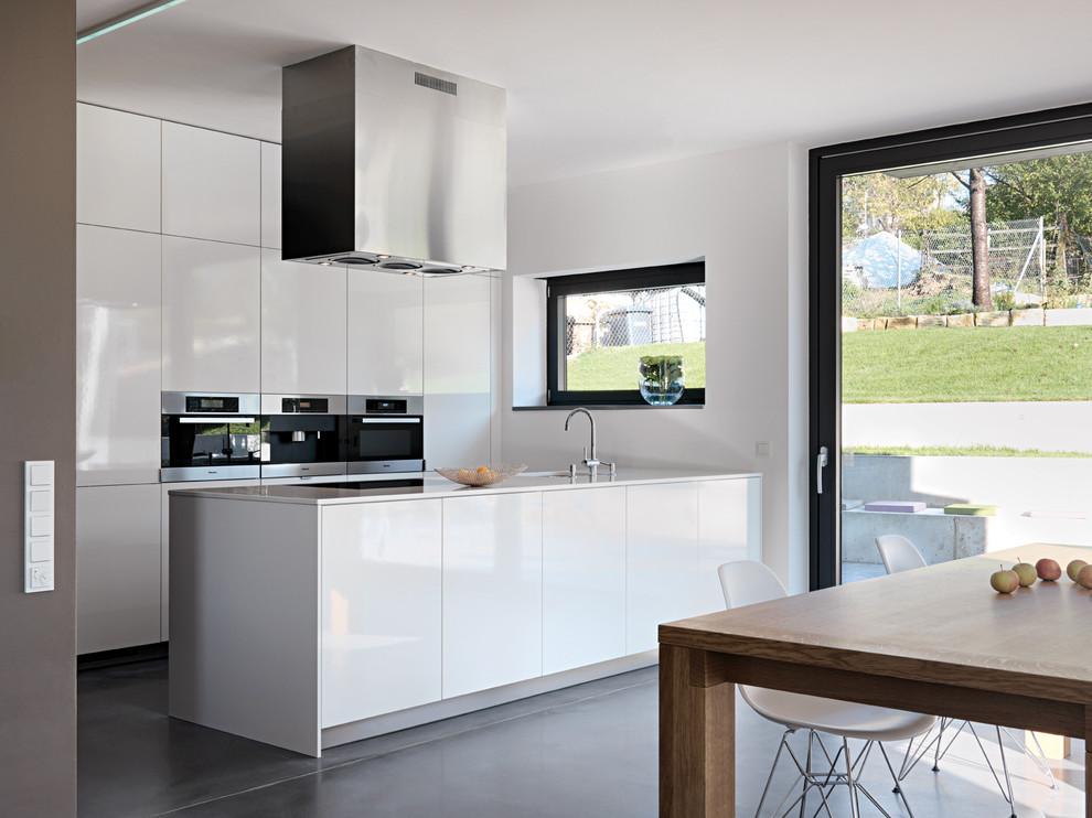 Offene, Mittelgroße Moderne Küche mit Küchengeräten aus Edelstahl, Unterbauwaschbecken, flächenbündigen Schrankfronten, weißen Schränken, Betonboden und Halbinsel in Stuttgart