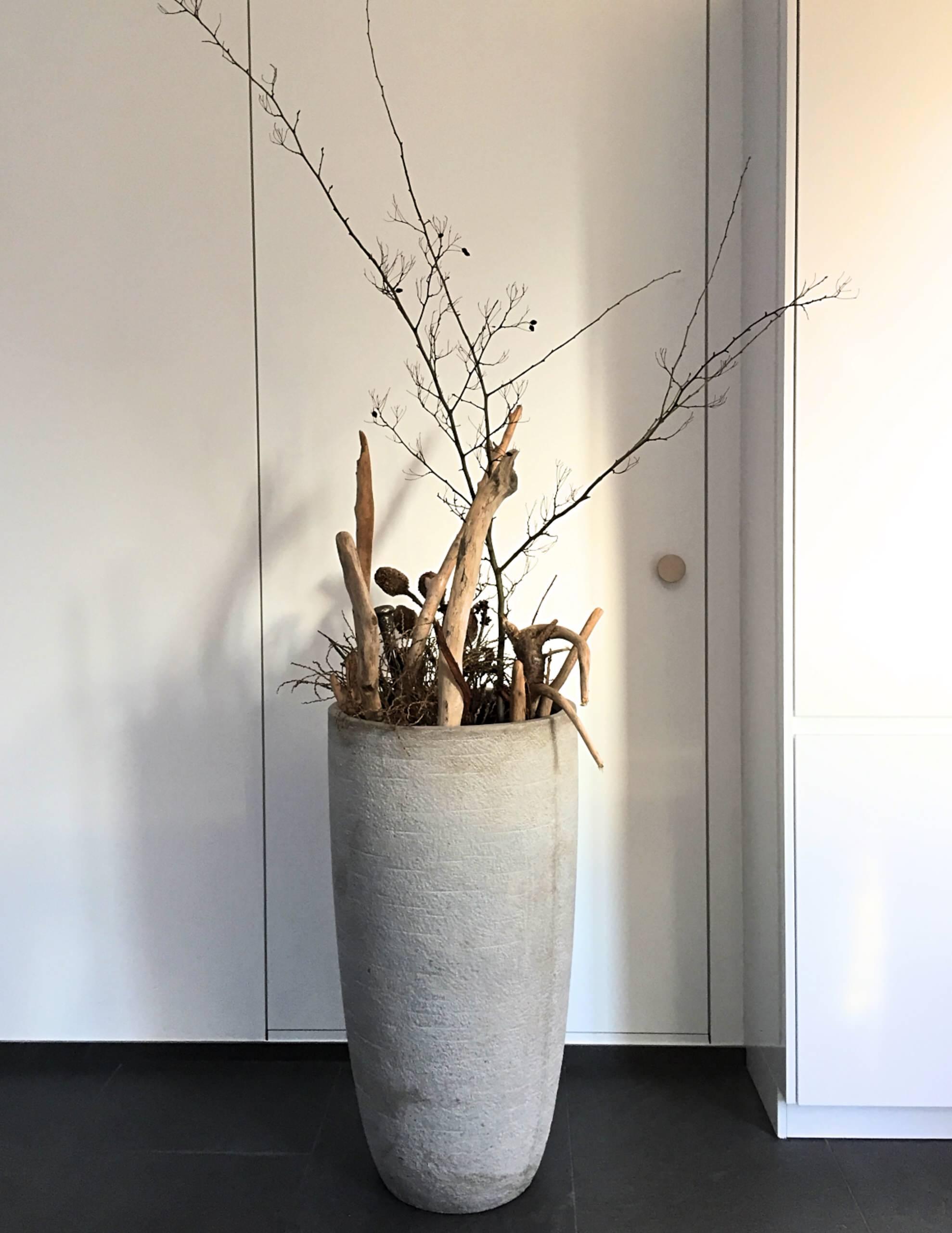 Solitärobjekt, Betonkübel mit Treibholz in einer großen Küche