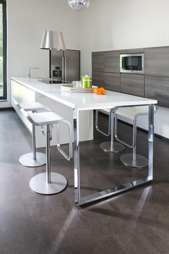 Mittelgroße Moderne Wohnküche in L-Form mit flächenbündigen Schrankfronten, hellen Holzschränken, Küchengeräten aus Edelstahl, Kücheninsel, braunem Boden und weißer Arbeitsplatte in Sonstige
