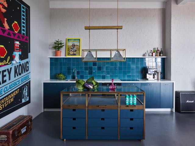 Einzeilige, Kleine Eklektische Küche mit flächenbündigen Schrankfronten, blauen Schränken, Glas-Arbeitsplatte, Küchenrückwand in Blau, Betonboden, Kücheninsel und Rückwand-Fenster in Berlin