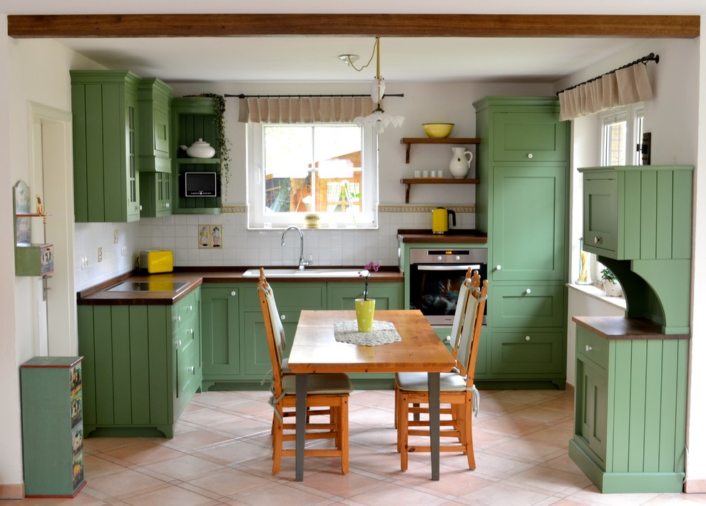 Large country eat-in kitchen photo in Berlin with a drop-in sink, green cabinets, white backsplash, stainless steel appliances, shaker cabinets, wood countertops, subway tile backsplash and no island