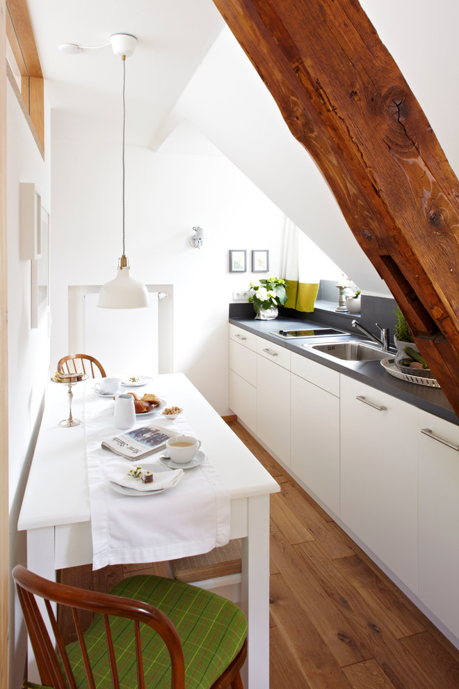 Inspiration for a small contemporary single-wall medium tone wood floor eat-in kitchen remodel in Munich with flat-panel cabinets, white cabinets, no island, a drop-in sink, gray backsplash and paneled appliances